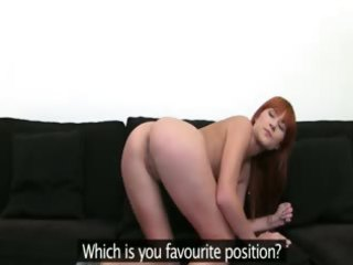 redhead princess posing on dark sofa